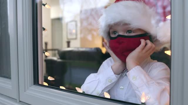 junge blick durch hausfenster während der covid-19 pandemie - weihnachtsmütze stock-videos und b-roll-filmmaterial