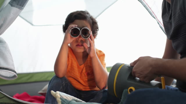young boy looking through homemade binoculars. - pillow stock videos & royalty-free footage