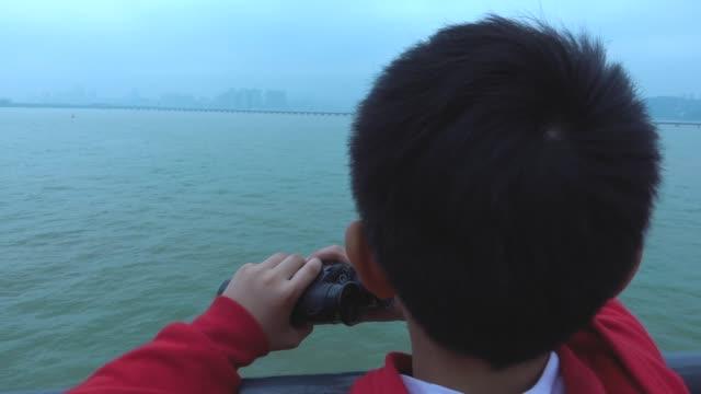 tourboat で双眼鏡を探している少年 - 指差す点の映像素材/bロール