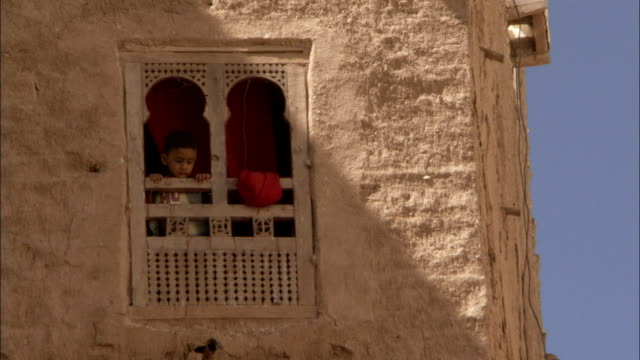 a young boy looks out of a decorative window of a mud brick apartment building. - yemen stock videos & royalty-free footage