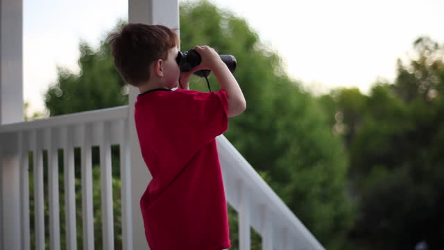 A young boy looks through binoculars from his front porch.