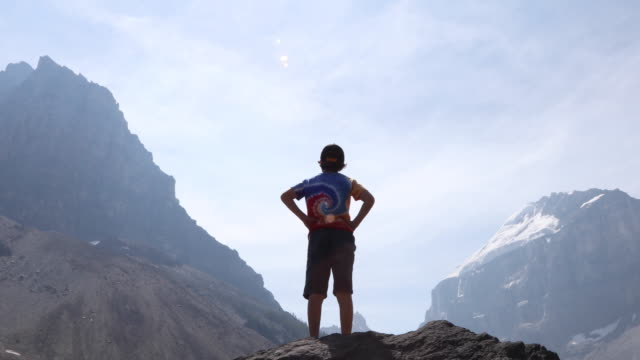 young boy looks towards distant mountains, from summit - grandangolo tecnica fotografica video stock e b–roll