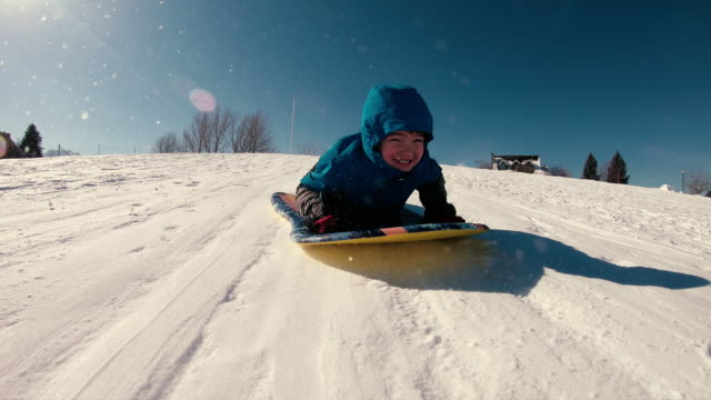 young boy loves snow sledding - winter sport stock videos & royalty-free footage