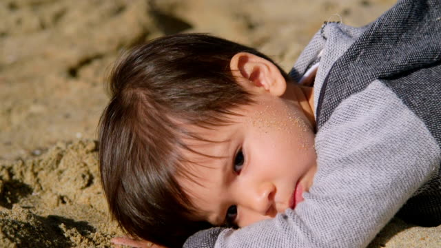Young Boy Lying on Sand