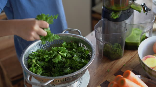 a young boy making a juice with a slow juicer, at home on the kitchen table. - kale stock videos and b-roll footage