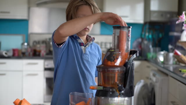 vidéos et rushes de a young boy making a juice with a slow juicer, at home on the kitchen table. - carotte