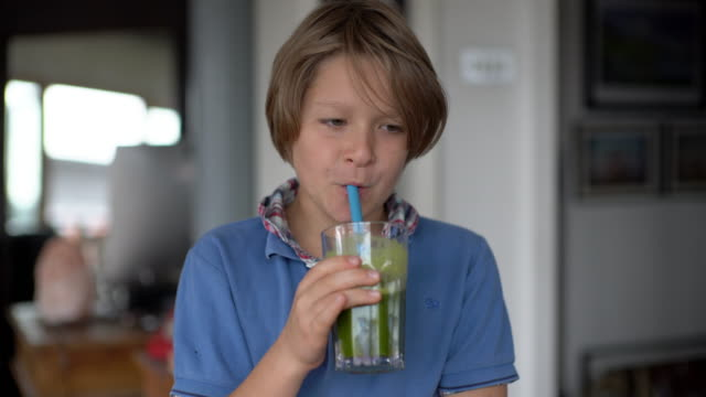 a young boy making a juice with a slow juicer, at home on the kitchen table. - cold drink stock videos and b-roll footage