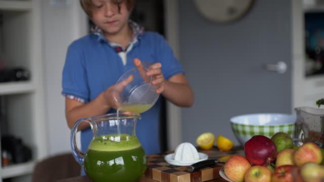 vídeos y material grabado en eventos de stock de a young boy making a juice with a slow juicer, at home on the kitchen table. - camisa de polo