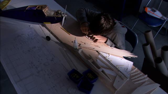 vídeos de stock e filmes b-roll de jovem rapaz fazendo um modelo de avião - cara para baixo