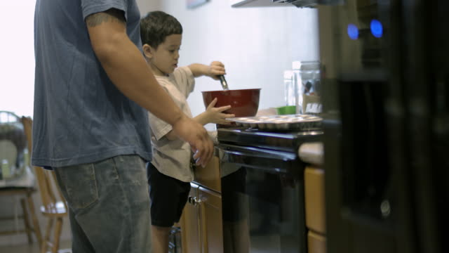 vídeos de stock e filmes b-roll de young boy making cup cakes in kitchen with dad's help - genderblend