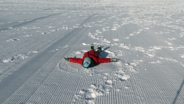 young boy making snow angel. - reclining stock videos & royalty-free footage