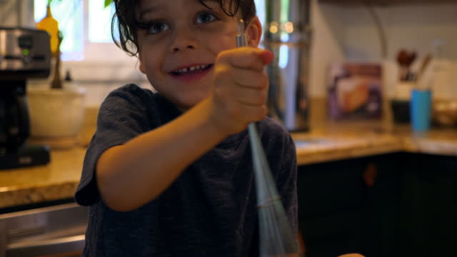 CU Young boy mixing eggs for breakfast in kitchen while father adds spices
