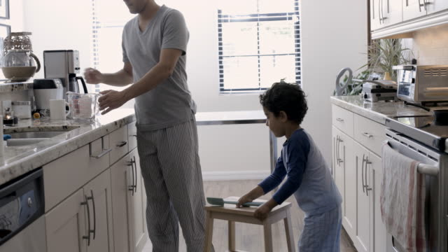 ws young boy moves stool and climbs up to help dad make breakfast - stool stock videos & royalty-free footage