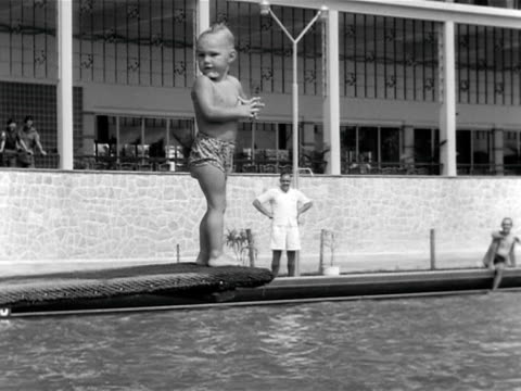 a young boy nervously jumps off a diving board into the swimming pool at the naafi building in singapore - paura video stock e b–roll