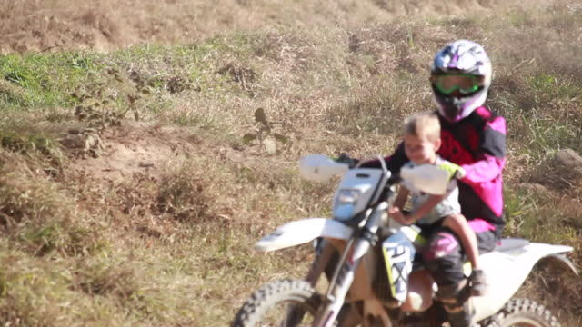 young boy on a dirt bike rides around on a dirt bike while a woman follows the boy on a dirt bike with another young boy riding with her around a dirt bike track. then she drives off of it and lifts the boy up. - kelly mason videos stock videos & royalty-free footage