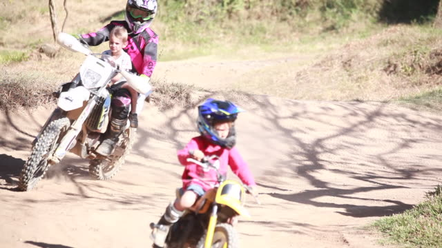 young boy on a dirt bike rides around on a dirt bike while a woman follows the boy on a dirt bike with another young boy riding with her around a dirt bike track. - kelly mason videos stock videos & royalty-free footage