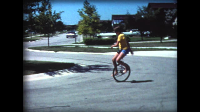 1977 young boy on unicycle riding around suburban street