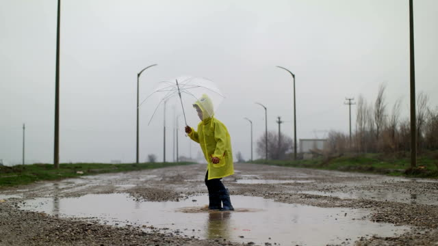 a young boy outside in the rain - wellington boot stock videos & royalty-free footage