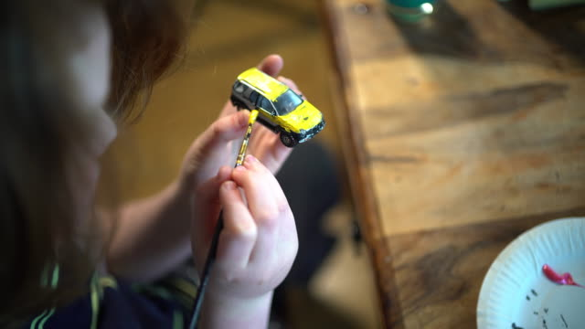 vídeos y material grabado en eventos de stock de a young boy painting his cars - pincel