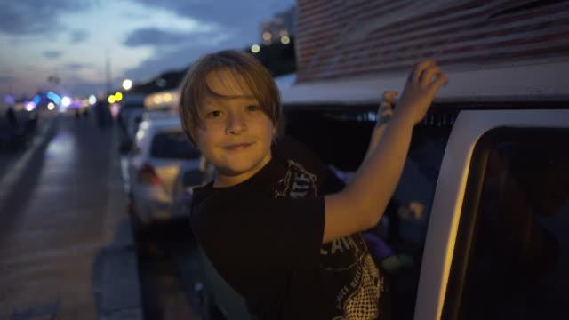 stockvideo's en b-roll-footage met a young boy peering out of his camper van. - tanden op elkaar klemmen