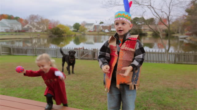 young boy performs a thanksgiving song while his younger sister distracts the family dog - vignette stock videos & royalty-free footage