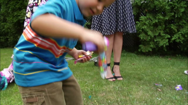 young boy picking up candy from lawn that has fallen out of broken pinata / smiling and displaying / new jersey - game show stock videos & royalty-free footage