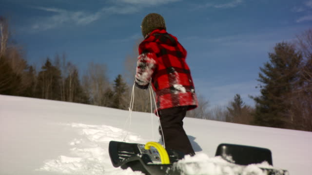MS Young boy picking up ropes of snow sled to run off  / Stowe, Vermont, United States