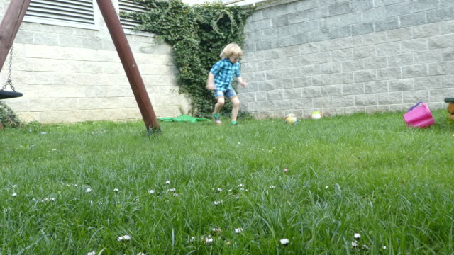young boy playing a ball in backyard. - only boys stock videos and b-roll footage