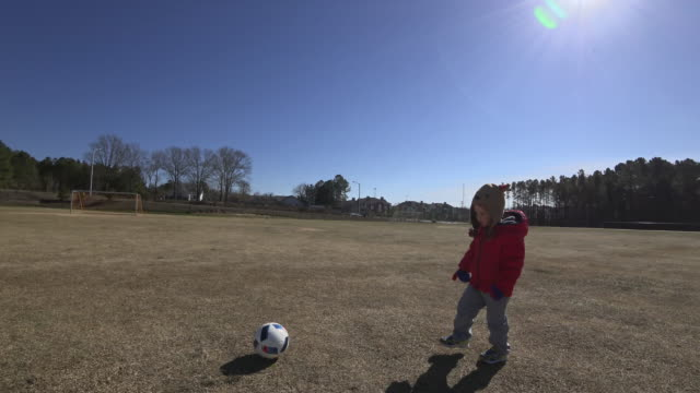 Young boy playing by himself on a soccer field