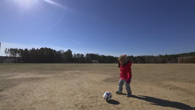 Kleiner Junge spielt alleine auf einem Fußballfeld