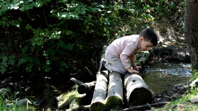 young boy playing by mountain river - böja sig bildbanksvideor och videomaterial från bakom kulisserna