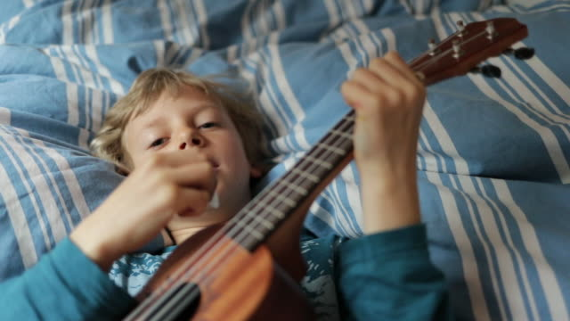 A young boy playing guitar on a bed