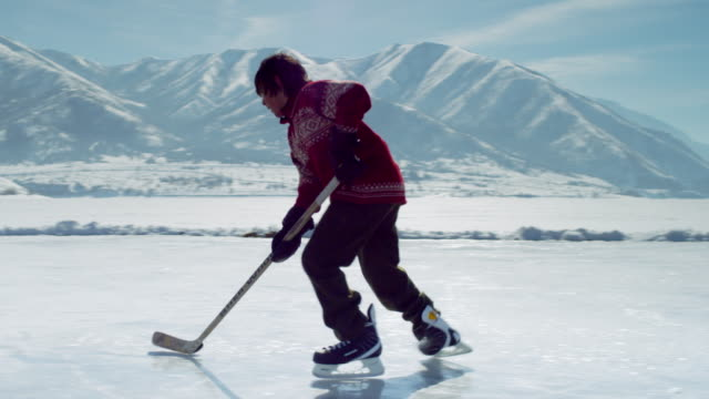 young boy playing hockey at an outdoor rink. - one teenage boy only stock videos & royalty-free footage