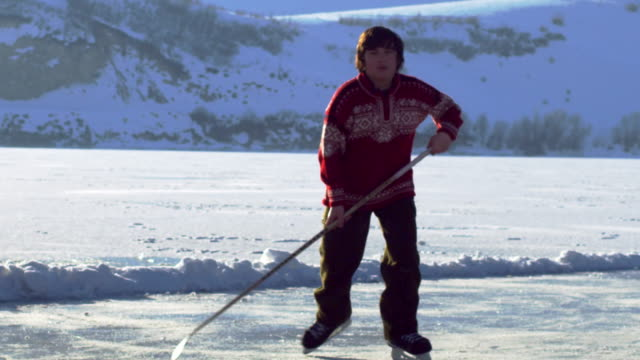 Young boy playing hockey on an outdoor ice rink.
