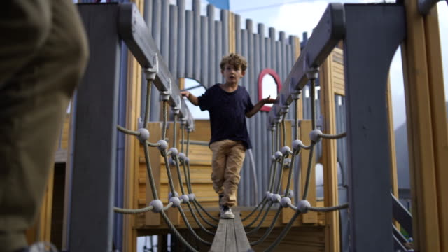 young boy playing in playground - children only stock videos & royalty-free footage