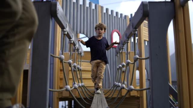 vidéos et rushes de jeune garçon jouant dans l'aire de jeux - children only