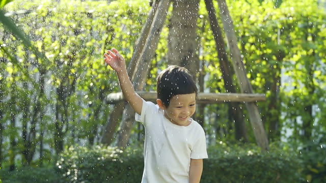 Young boy playing in water sprinkler at home in his back yard on hot summer day.(Shooting with slow motion vdo camera)