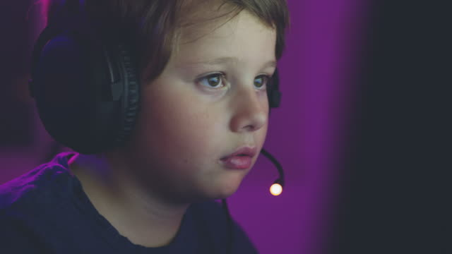 young boy playing online computer games - headset stock videos & royalty-free footage