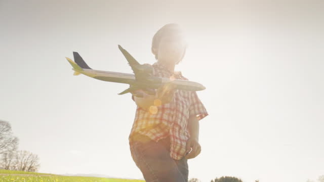 a young boy playing with an airplane in a grass field - model aeroplane stock videos & royalty-free footage