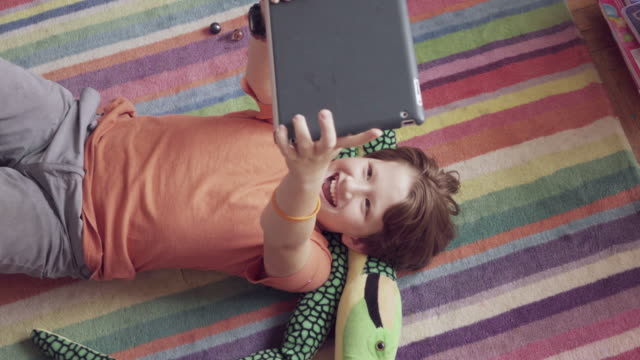 MS Young boy playing with digital tablet on carpet