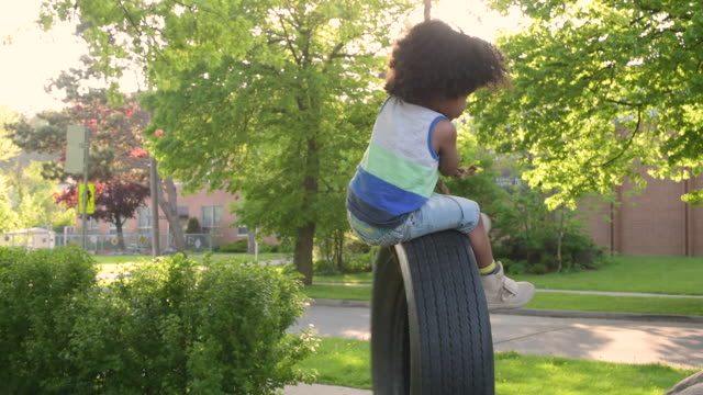 Young boy playing with old white wall tire swing