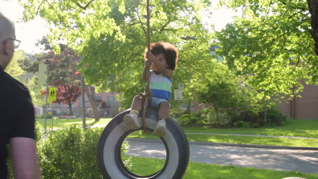 young boy playing with old white wall tire swing - 屋外遊具点の映像素材/bロール