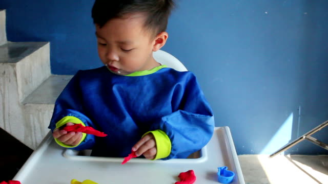 Young boy playing with play dough