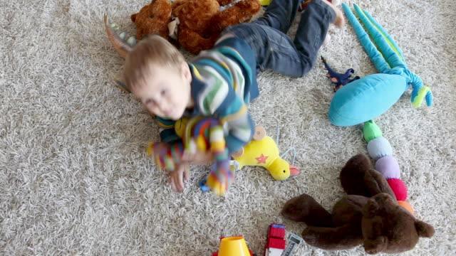 young boy playing with soft toys on living room rug, high angle - ラグ点の映像素材/bロール