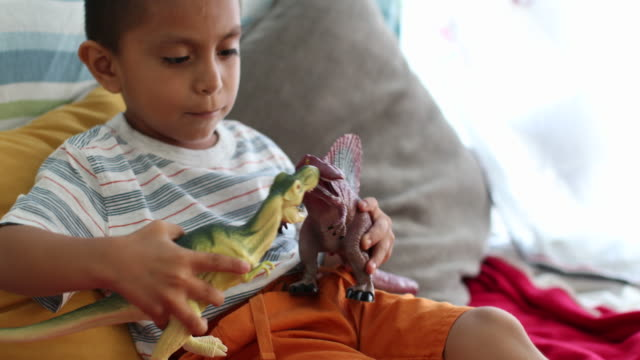cu young boy playing with toy dinosaurs. - pillow stock videos and b-roll footage
