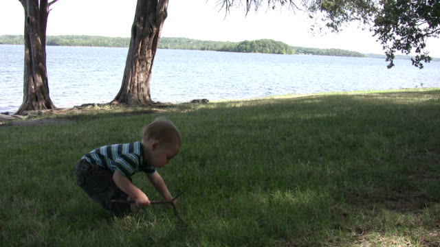 young boy plays at the edge of lake hd - bending stock videos & royalty-free footage