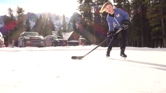 Young boy plays ice hockey, at mountain pond