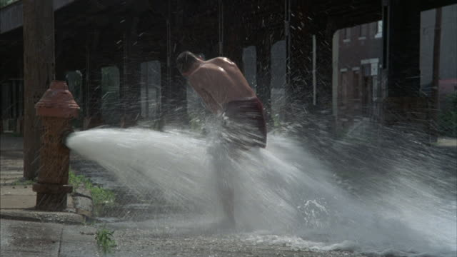 a young boy plays in the gushing water  of a fire hydrant. - männlicher teenager allein stock-videos und b-roll-filmmaterial
