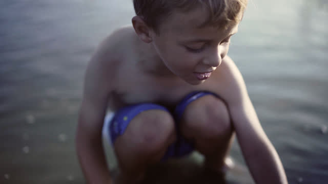 stockvideo's en b-roll-footage met young boy plays with red bucket in tide pool at dawn. - emmer