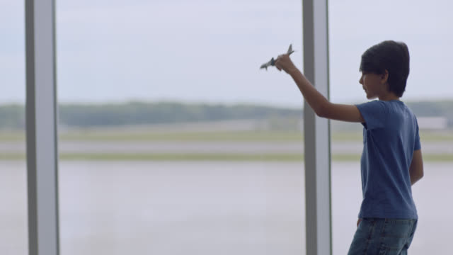 SLO MO. Young boy plays with toy airplane near gate window in airport terminal.